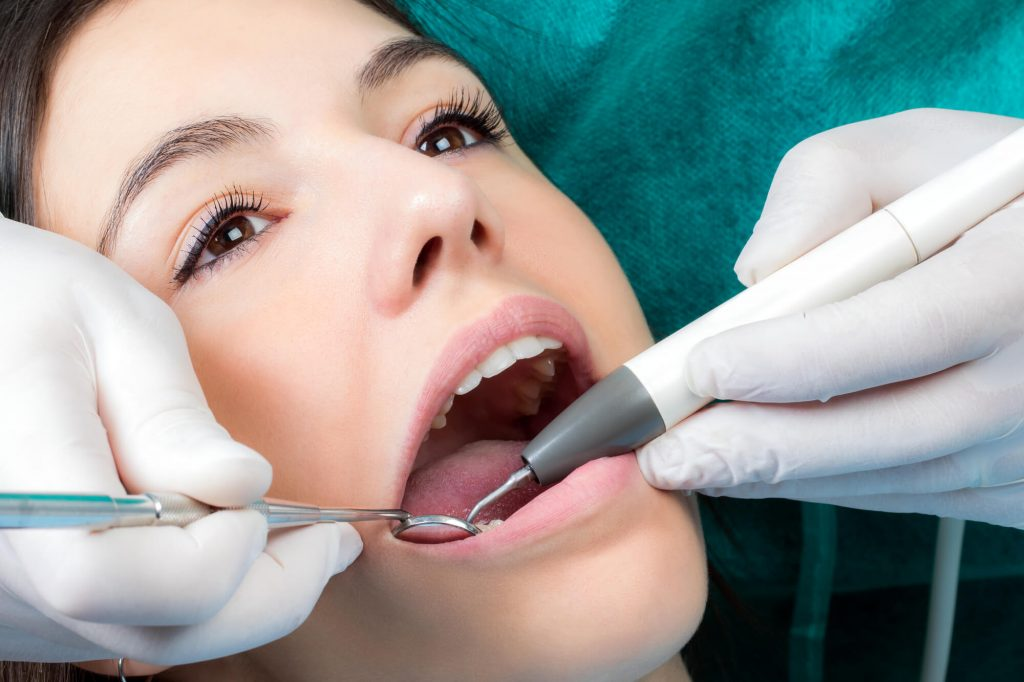 the Best dentist Fort Pierce examining a woman's mouth