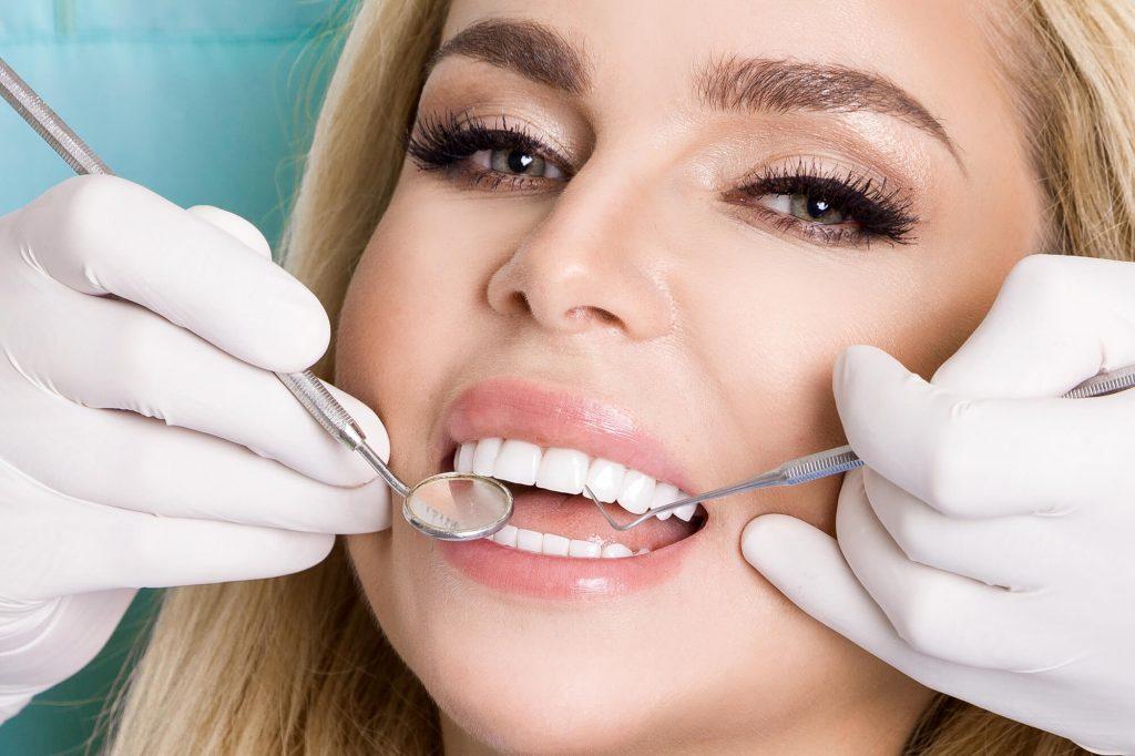 woman having her teeth checked veneers Fort Pierce