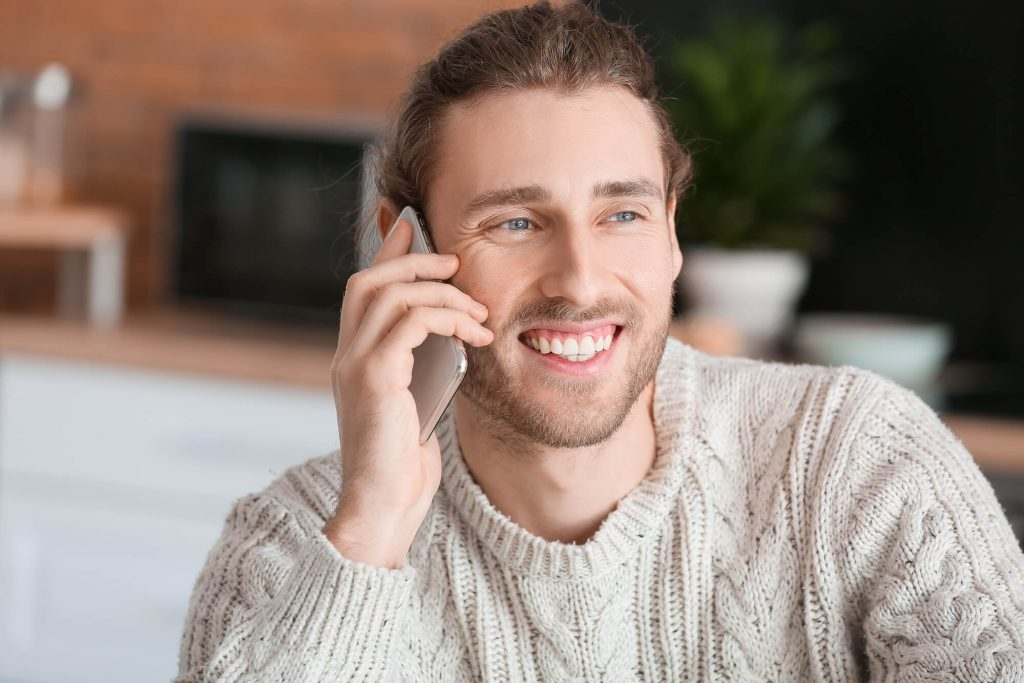 man using his phone and smiling with veneers on his teeth