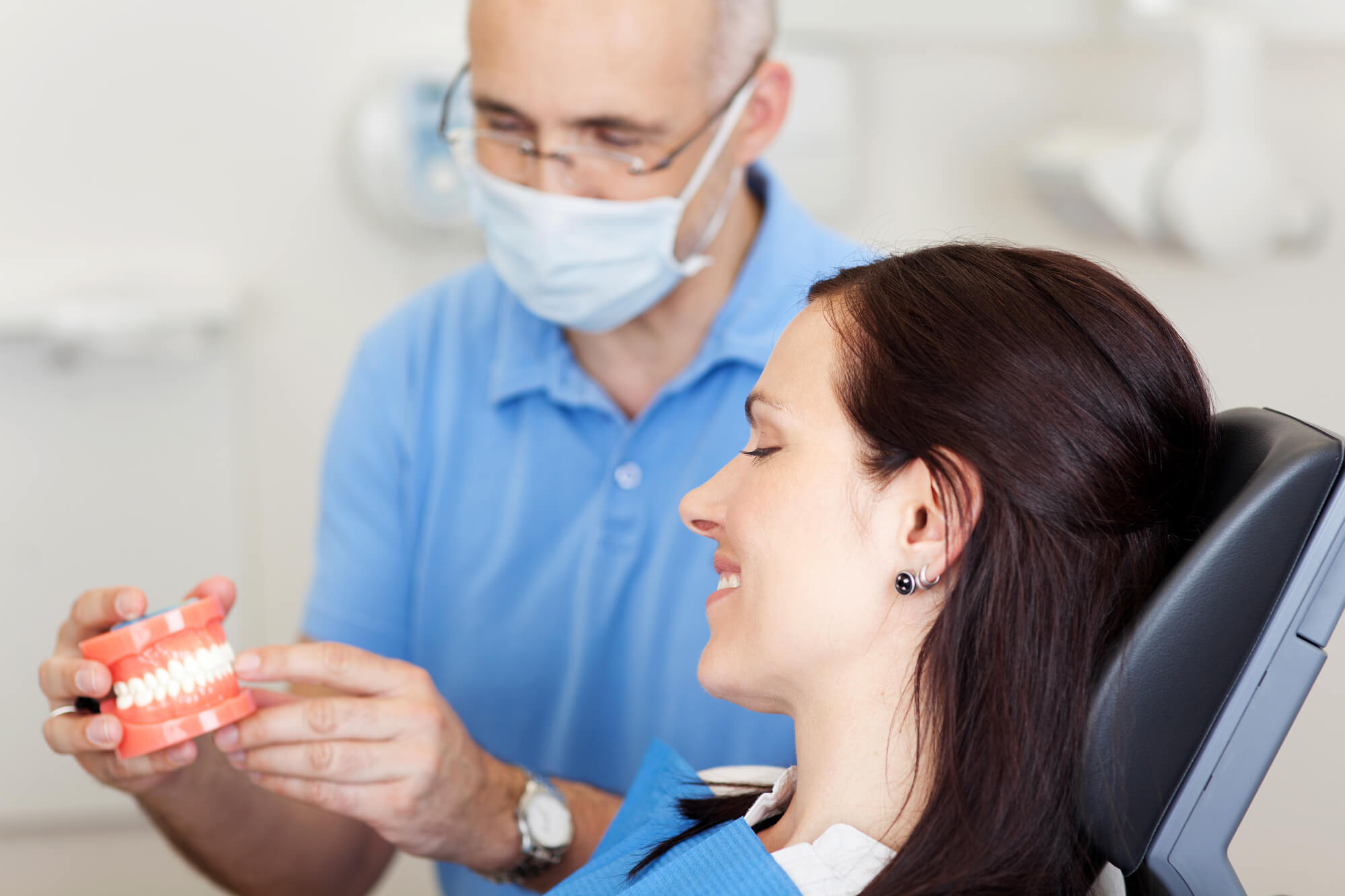 Dentist showing a girl a set of Port St. Lucie Dentures